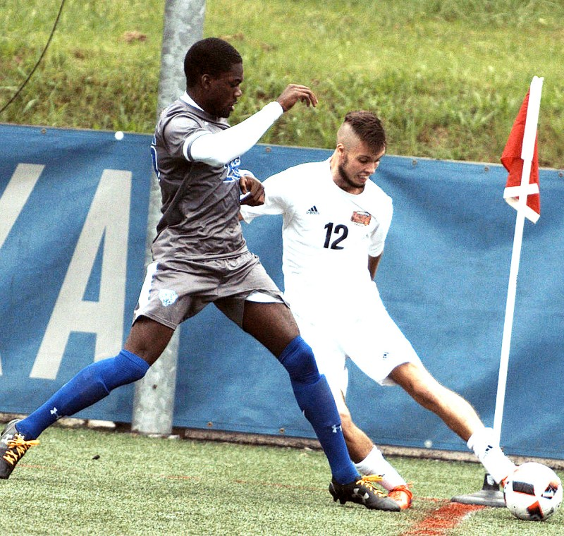 University of the District of Columbia defender Liam Haycock (12) attempts to avoid New York Institute of Technology defender Niyah Highsmith at Georgetown University's Cooper Field in northwest D.C. on Saturday, Oct. 1. NYIT defeated UDC 3-0. /Photo by John E. De Freitas