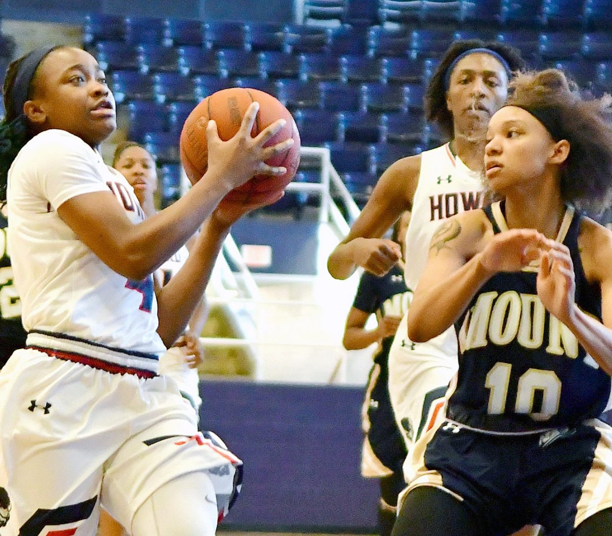 Howard Lady Bison guard Ayonna Williams, a product of D.C.'s Ballou Senior High School, drives past Mount St. Mary's Mountaineers guard Ashlee White in the second quarter of Howard's 95-62 win at Burr Gymnasium in Northwest on Saturday, Dec. 10. /Photo by John E. De Freitas