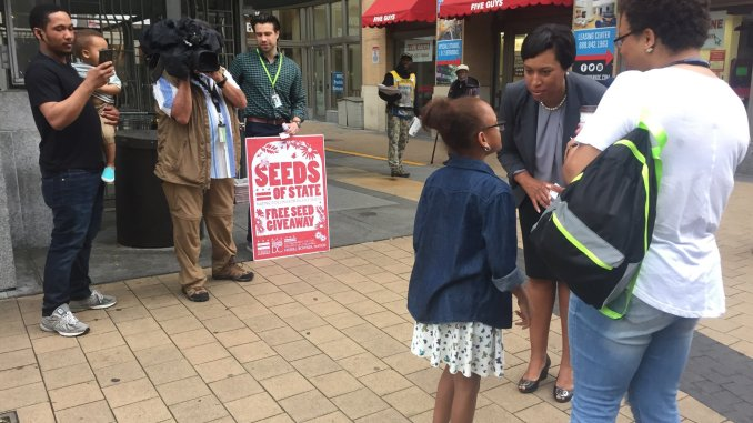 D.C. Mayor Muriel Bowser helps distribute free pollinator plant seeds at Metro stations across the city on April 21, the day before Earth Day. (Courtesy of DOEE)