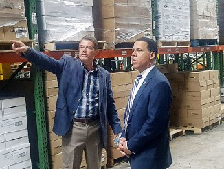 Rep. Anthony Brown (right) stands with Chris Umstot inside Eastern Food Services warehouse April 19 to look at the company's operation. The American Gaming Association began its nationwide tour at the Laurel establishment to tout how casinos partner with local small businesses. (William J. Ford/The Washington Informer)