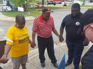 Fairmount Heights, Maryland, mayoral candidate Lillie Thompson-Martin (in yellow shirt) stands in a prayer circle outside the town municipal building May 1. Fairmount Heights was one of 11 towns holding local elections in Prince George's County. (William J. Ford/The Washington Informer)