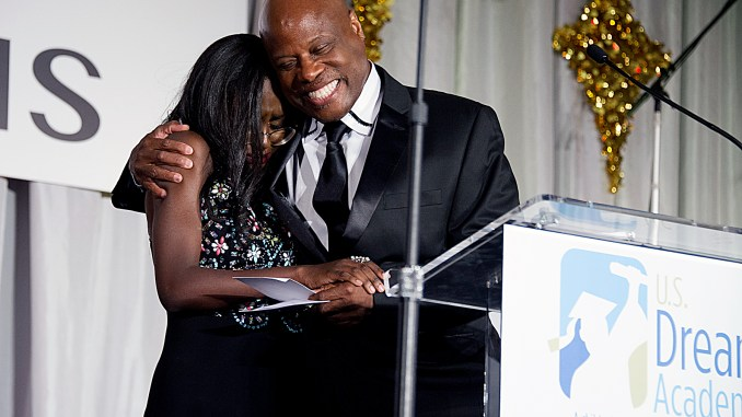 """Former Dream Academy's Christine Baron receives a special gift from Wintley Phipps, founder and CEO of the U.S. Dream Academy, during the academy's 16th annual """"Igniting Dreams"""" gala at the Washington Renaissance Hotel in Northwest on June 6. (Lateef Mangum/The Washington Informer)"""
