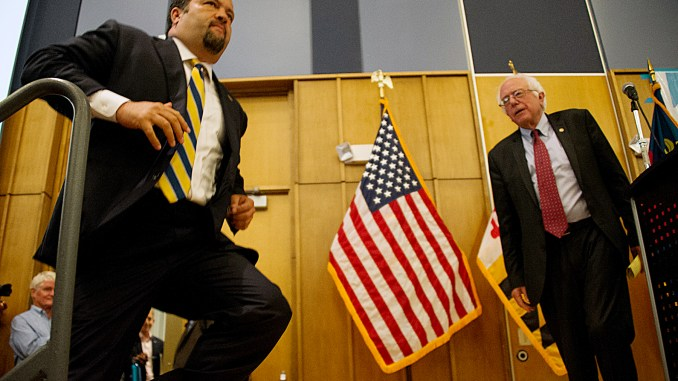 Ben Jealous, a Democratic candidate for Maryland governor, jumps onstage after a rousing introduction on July 14 in Silver Spring, Md., by former presidential candidate, Sen. Bernie Sanders. (Lateef Mangum/The Washington Informer)