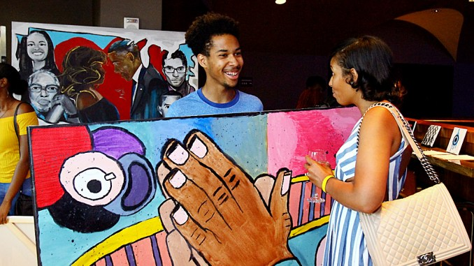 "Justin Lee, 20, discusses his artwork, titled ""Hands of Hope,"" with the audience of the 2017 P.A.I.N.T.S. Arts Leadership Program Youth Arts Showcase, June 30 at the Howard Theatre in northwest D.C. Lee describes the hands in his work representing a prayer to God and hopes the piece will motivate others to believe that anything is possible when in communication with God. (E Watson/EDI Photo)"