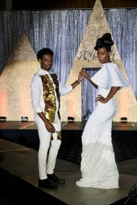 "Designer and wardrobe stylist Jarmal Harris poses with one of his models during the finale of his 10th annual ""Royalty"" fashion show at The Sphinx Club in northwest D.C. on Aug. 5. (Roy Lewis/The Washington Informer)"