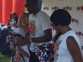 "Washington Wizards guard John Wall helps a child put on a backpack during his John Wall Family Foundation's annual ""Back to School"" event at the Rosedale Community Center in northwest D.C. on Aug. 18. (William J. Ford/The Washington Informer)"