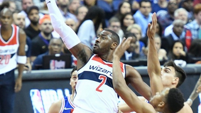 Washington Wizards point guard John Wall goes in for a layup against two Philadelphia 76ers defenders during the first quarter of the Wizards' 120-115 win at Capital One Arena in D.C. on Oct. 18. (John De Freitas/The Washington Informer)