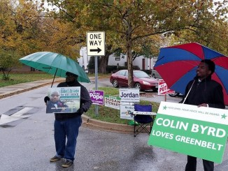 City of Greenbelt candidates Colin Byrd (right) and Brandon R. Gordon stand in the rain outside a polling center waiting to chat with prospective voters on Election Day, Nov. 7. (William J. Ford/The Washington Informer)
