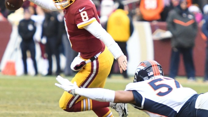 Washington Redskins quarterback Kirk Cousins slips away from Denver Broncos defensive end DeMarcus Walker during the Redskins' 27-11 win at FedEx Field in Landover, Md., on Dec. 24. (John E. De Freitas/The Washington Informer)
