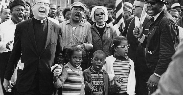 Martin Luther King Jr. was a champion for equity in education. Ralph Abernathy and his wife Juanita Abernathy (not pictured) follow with Dr. and Mrs. Martin Luther King, Jr., as the Abernathy children march on the front line, leading the Selma to Montgomery March in 1965. The children are (from left) Donzaleigh Abernathy (in striped sweater), Ralph David Abernathy III and Juandalynn R. Abernathy (in glasses). The name of the White minister in the photo is unknown. (Abernathy family photos/Wikipedia Commons)