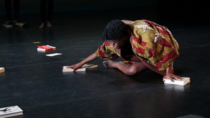 "Ronya-Lee Anderson stretches on the floor to perform a piece she created called ""Canon"" during a dress rehearsal at the Clarice Smith Performing Arts Center in College Park on Jan. 26. (Roy Lewis/The Washington Informer)"