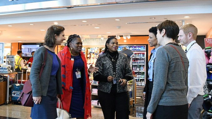 """Juanita """"BZB"""" Britton (second from left), partner and senior vice president of Paradies-BZB, DC, LLC, along with Nivlem Dickens (third from left), general manager of the Washingtonian at Ronald Reagan Washington National Airport in D.C., speak about their business at the airport with a group from France on Feb. 27. (Roy Lewis/The Washington Informer)"""