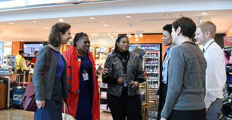 "Juanita ""BZB"" Britton (second from left), partner and senior vice president of Paradies-BZB, DC, LLC, along with Nivlem Dickens (third from left), general manager of the Washingtonian at Ronald Reagan Washington National Airport in D.C., speak about their business at the airport with a group from France on Feb. 27. (Roy Lewis/The Washington Informer)"