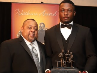 Quincy Patterson II, a senior quarterback at Eric Solorio Academy High School in Chicago who has committed to Virginia Tech, is presented with a trophy honoring the nation's top African-American male high school senior student-athlete by J. Everette Pearsall, executive director of the National Alliance of African American Athletes.