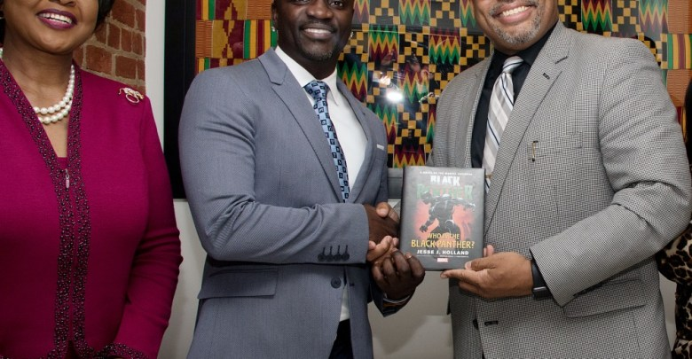 """Jesse L. Holland (right), author of the book """"Black Panther: Who Is the Black Panther?"""", presents singer Akon (center) with a copy of the book as Arikana Chihombori-Quao, African Union Ambassador to the U.S., poses with them for a photograph at the Africa House in northwest D.C. (Shevry Lassiter/The Washington Informer)"""