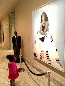 Parker Curry, 2, stands in front of the National Portrait Gallery painting of Michelle Obama. (Courtesy of Ben Hines via Facebook)