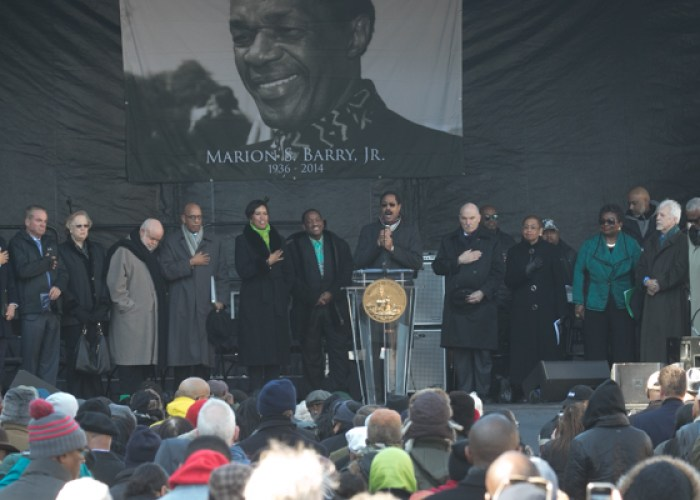 Prominent speakers on the dais including Mayor Muriel Bowser stand for the National anthem during the Marion Barry Jr. statue unveiling on Saturday, March 3. (Shevry Lassiter/The Washington Informer)