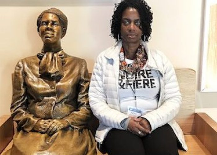 A statue of Harriet Tubman, in her later years, sitting on a bench, allows visitors to sit next to her, including attorney Deborah Boddie, before exiting the center. (DR Barnes/The Washington Informer)