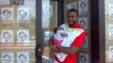 Alexander Mosby holds his month-old daughter Gabby in front of his District Culture store in southeast D.C. (Courtesy of East Bank DC)