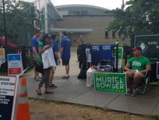 Volunteers for D.C. Mayor Muriel Bowser and city Councilman Charles Allen wait to speak with voters outside King Greenleaf Recreation Center in Southwest during the city's primary election on June 19. (William J. Ford/The Washington Informer)