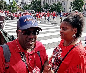 """Tony Johnson (left) and girlfriend Andrea Crichlow of Southeast follow the Washington Capitals' moniker, """"Rock the Red"""" at a June 12 parade to celebrate the team winning the Stanley Cup championship. (William J. Ford/The Washington Informer)"""