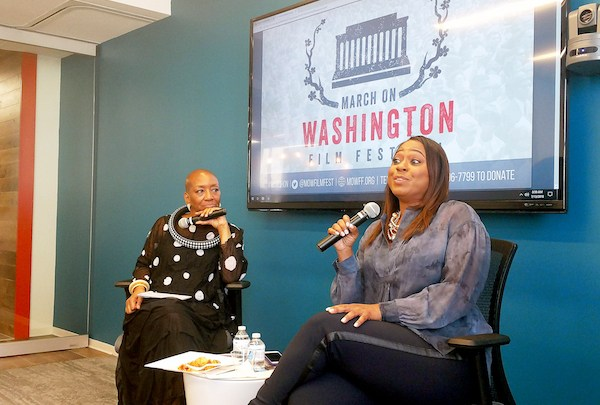 """Isisara Bey (left), artistic director of the March on Washington Film Festival, interviews hairstylist Camille Friend, who worked on the set of """"Black Panther,"""" at the festival's """"Breakfast with a Friend"""" event in the offices of the Raben Group in D.C. on July 13. (Brenda C. Siler/The Washington Informer)"""