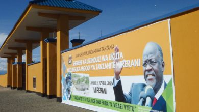 A banner of Tanzanian President John Joseph Magufuli adorns the wall at the only entrance of newly built 24-kilometer wall around the country's tanzanite mines to prevent smuggling of the precious violet-blue stones, which are unique to the East African country in Merelani, near Mount Kilimanjaro on April 11, 2018. (Joseph Lyimo/AFP/Getty Images)