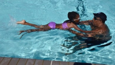 Aquatics instructor Bobby Broome guides Zoë Randolph across the swimming pool on the final day of a water safety camp at Joint Base Andrews in Prince George's County, Maryland, on Aug. 24. (Robert Roberts/The Washington Informer)