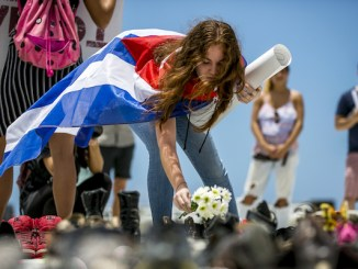 A demonstrator places flowers inside an empty pair of shoes displayed outside the Capital building during a protest against the government's reporting of the death toll from Hurricane Maria in San Juan, Puerto Rico, on Friday, June 1, 2018. Hurricane Maria probably killed about 5,000 people in Puerto Rico last year even though the official count remains at just 64, according to a Harvard University study released Tuesday. Photographer: Xavier Garcia/Bloomberg