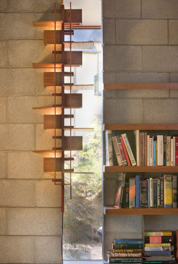 Natural light filters through slit windows, imbued with additional texture from a wooden sconce.