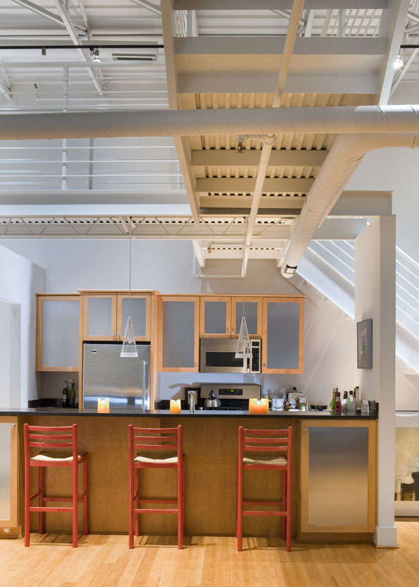 Stools pulled up to the kitchen's granite-topped island in view of stainless-steel cabinets and appliances.