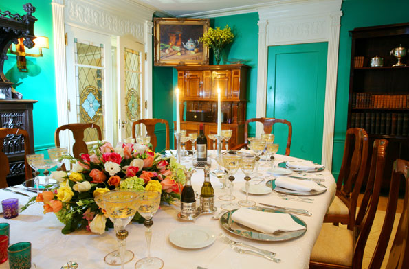 The dining room, painted bright green by the previous owners, centers on a long table and Queen Anne-style chairs.