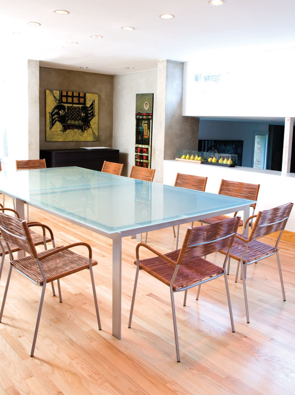 The large glass table in the dining room  serves not only as a contemporary  statement piece, but also provides ample  seating for family and friends. (Photo by John Heale)