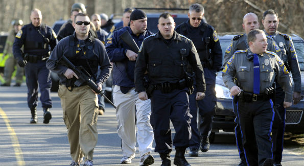 Law enforcement canvasses the surrounding areas following the shooting. (AP Photo/Jessica Hill)