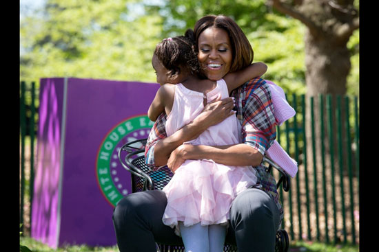 First lady Michelle Obama hugs a child (Photo by Chuck Kennedy)