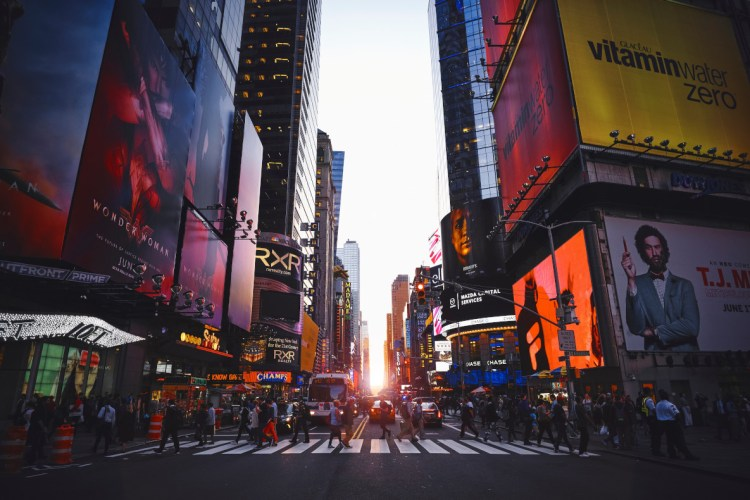A photo of a crossing in New York around time of sunset
