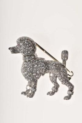 Poodle pin brooch/Cartier Paris, 1958/Platino, oro blanco. Diamantes corte redondos, brillantes y tipo baguette. Rubíes (ojos). Onyx (nariz). La cola y una pata son movibles.