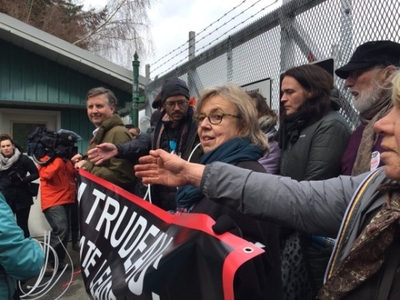 May, centre, and Stewart, left, lined up with other protesters against a gate at a Trans Mountain worksite — violating a court-ordered injunction to stay away from the company properties. (Courtesy of Rafferty Baker/CBC)