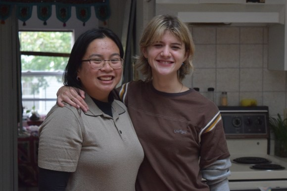 Two woman stand together for a photo in their kitchen.