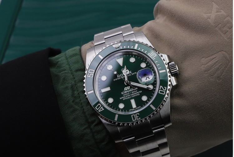 Man checking the time on a Rolex Men's watch with a green dial