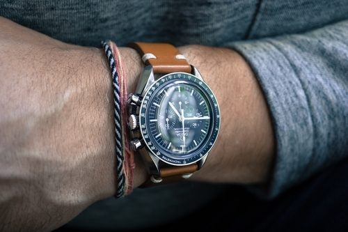 Man in casual clothing wearing an Omega dive watch with a stylish blue dial