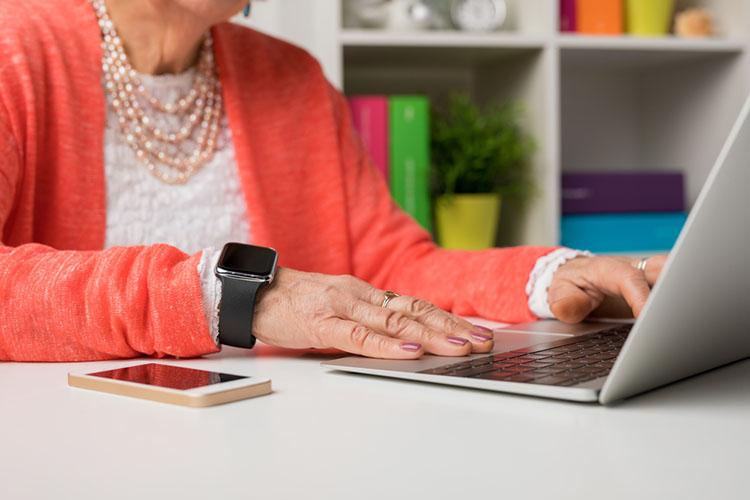 senior using smartwatch, smartphone and laptop