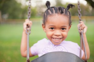 Girl in an infant swing