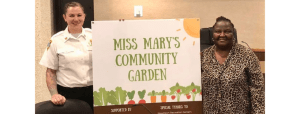 Katie Thielmeyer, Woodlawn Firefighter/Paramedic with Mary A. Wagner and sign for Miss Mary's Community Garden presented at Woodlawn village council meeting