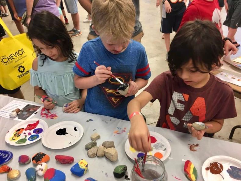 three kids painting rocks