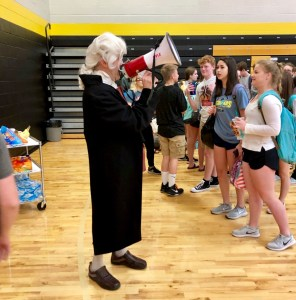 man dressed up like George Washington with megaphone talking to students