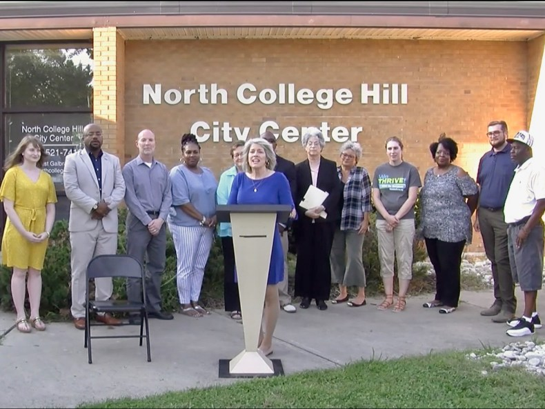 group standing in front of podium with north college hill city center behind them
