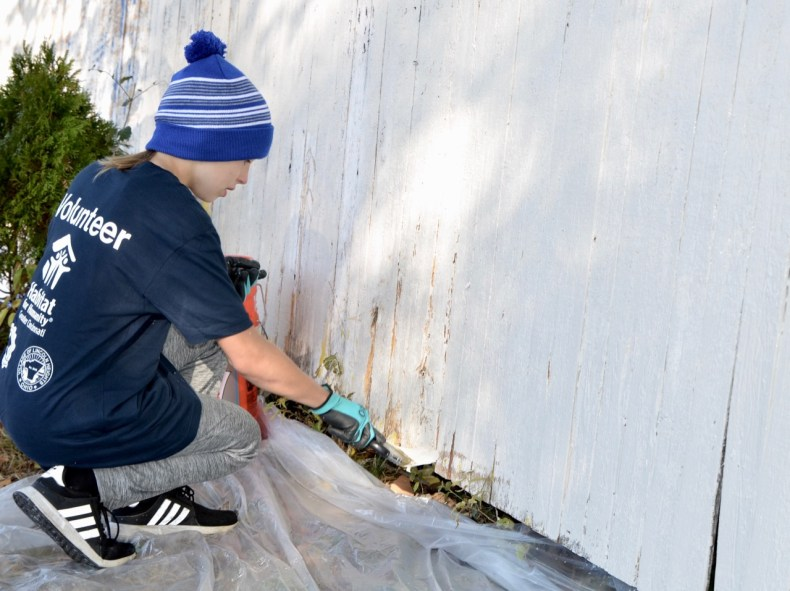 young volunteer painting a fence white