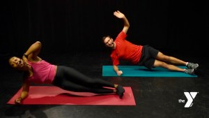 adult female and adult male in side lying yoga pose on yoga mats