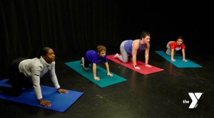 yoga class with two young boys and two adult female instructors, all kneeling on yoga mats